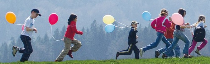 A group children with balloons running on a hill.