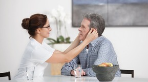 Homecare, Oxygen patientsitting on a table in a living room at home female nurse helping him with his nasal cannula, smiling, explaining
