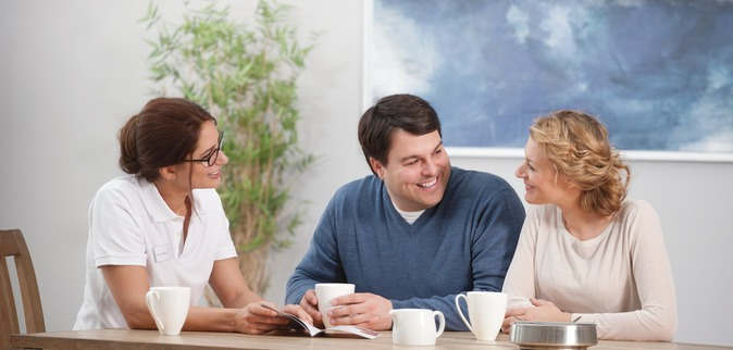 Homecare, Sleep patient sitting on a table in his living room  with a female nurse and his wife, nurse explaining  and informing, smiling